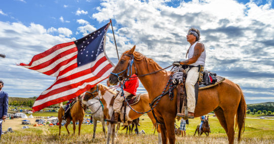 water-defenders-on-horseback-carrying-a-replica-battle-flag-of-the-one-taken-from-general-custer-8-sept-2016-rob-wilson-for-bold-alliance-1